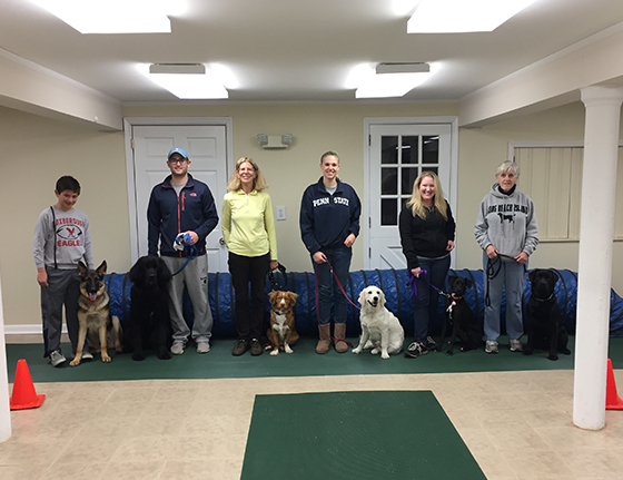 A group of proud dog owners and their pets posing at Canine Good Citizen Certification Ceremony