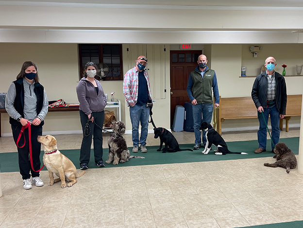 Proud dog owners with their pets at a training class graduation ceremony