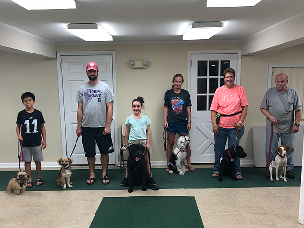 Three proud dog owners with their pets at a training class graduation ceremony